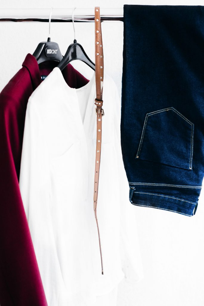 Jeans hanging on a clothes rack beside a thin brown belt and a white top and a burgundy blazer