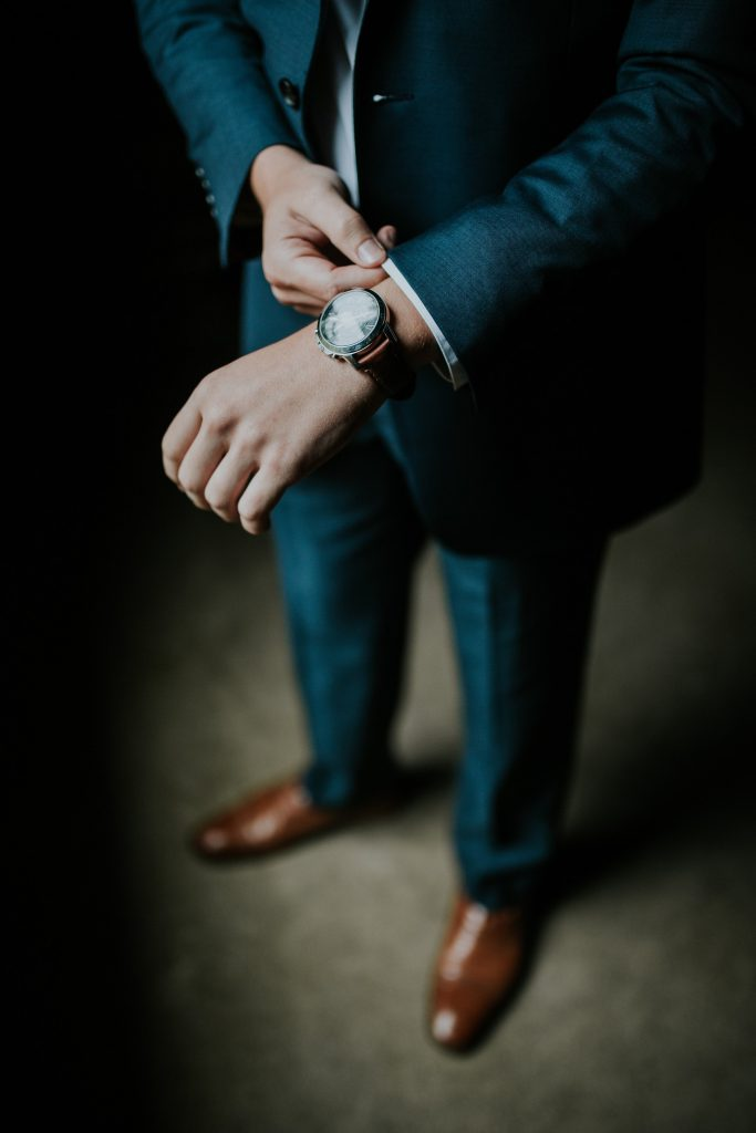 man wearing navy suit and watch with brown leather strap