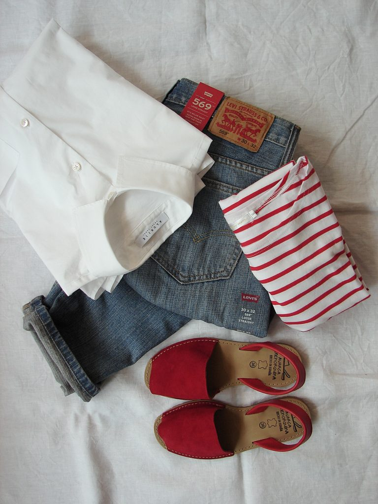 Levi's jeans flatlay with a red and white striped top and a pair of red sandals and a white button down shirt