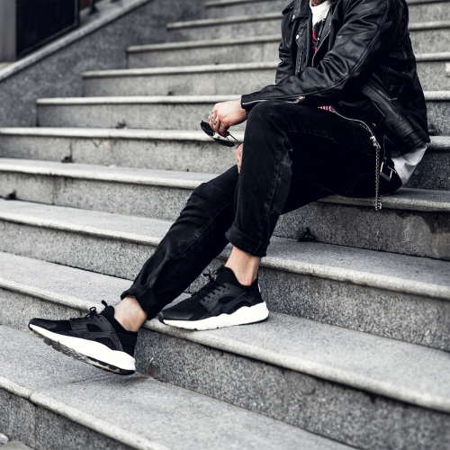 Young man wearing athletic shoes and leather motorcycle jacket while sitting on steps