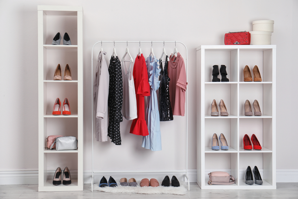 Clothes hanging on a rack with a shoe organizer shelf on each side filled with heels in an assortment of colors