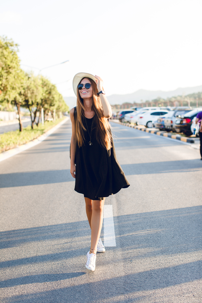 woman wearing black sleeveless flowy dress with white hat and white sneakers