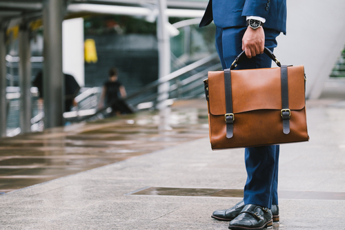 business man wearing suit and carrying leather bag