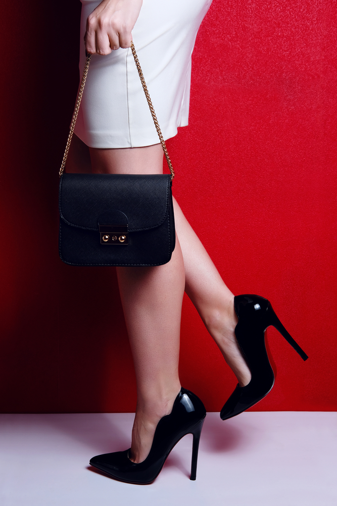 woman wearing black stiletto heels and white skirt and carrying a timeless black purse