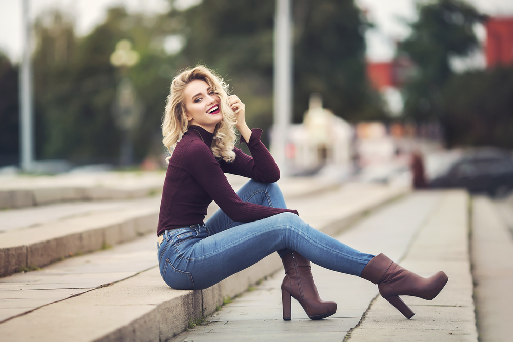 blonde girl sitting on steps wearing jeans with tall booties and a plum turtleneck top