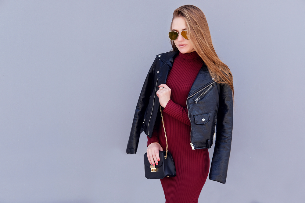 brunette girl wearing black motorcycle jacket and burgundy dress with black cross body bag