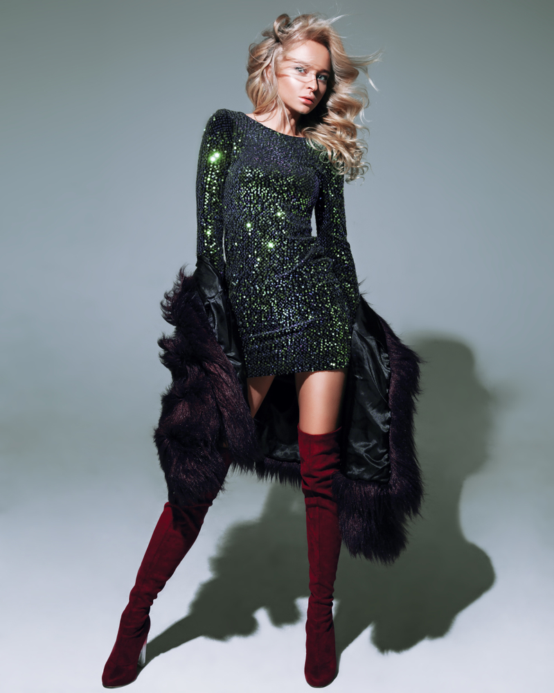 girl wearing classic sequin black formal dress with fur coat and thigh high burgundy boots