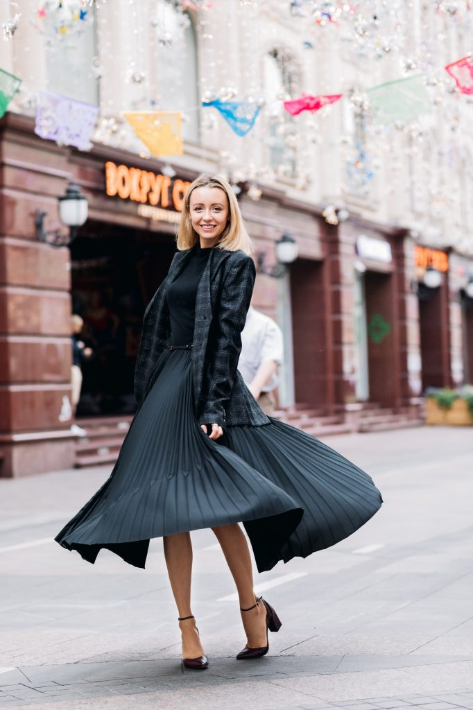 girl wearing pleated long silk skirt with black jacket and black heels