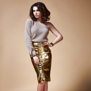 Woman wearing gold metallic skirt and one shoulder sweater