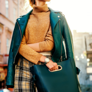 Woman wearing emerald green moto jacket and brown turtleneck and holding green purse